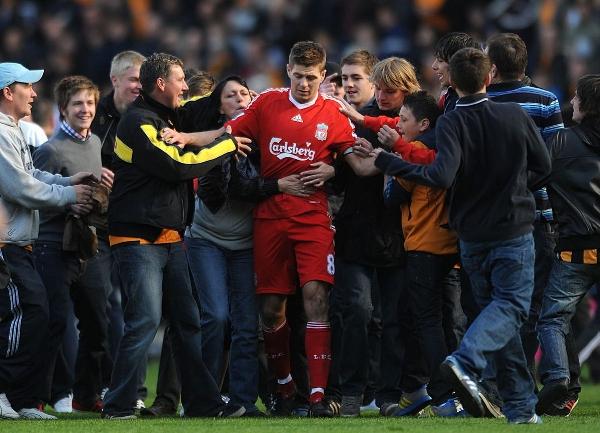 Болельщики окружили Стивена Джеррарда из «Ливерпуля», когда он уходил с поля после игры 2010 года против футбольного клуба «Халл Сити». Фото: Анна Гоуторп/PA/Getty Images.
